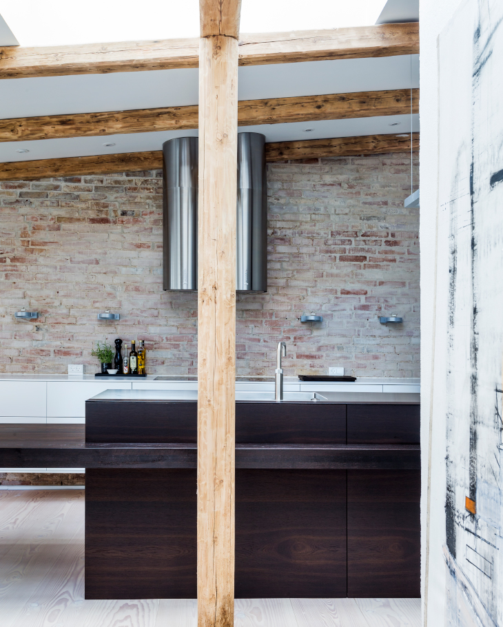The exposed beams and rough brickwork reflect the building's past and interact with the brand new Multiform kitchen.
